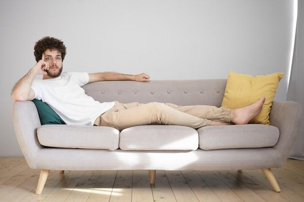 Atractivo joven caucásico con peinado ondulado y espesa barba descansando en casa después del trabajo, descalzo en el sofá de su apartamento de soltero, con expresión pensativa,