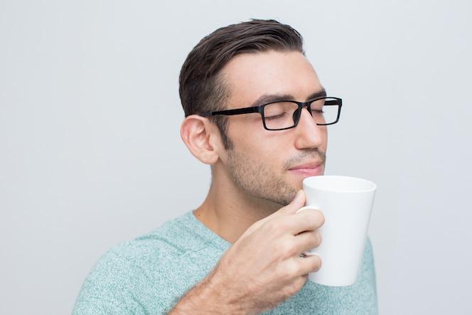 Atractivo joven disfrutando de olor de té
