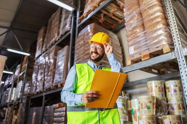 Atractivo joven empresario barbudo sonriente en chaleco con casco protector en la cabeza sosteniendo documentos importantes mientras está de pie en el almacén.
