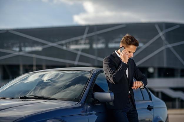 Atractivo joven empresario exitoso en un traje de negocios y ver en la mano hablando por teléfono inteligente cerca de su automóvil