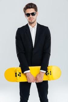 Atractivo joven empresario en traje negro con patineta amarilla sobre pared gris