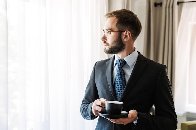 Atractivo joven empresario vistiendo traje de pie en la habitación del hotel, sosteniendo una taza de café