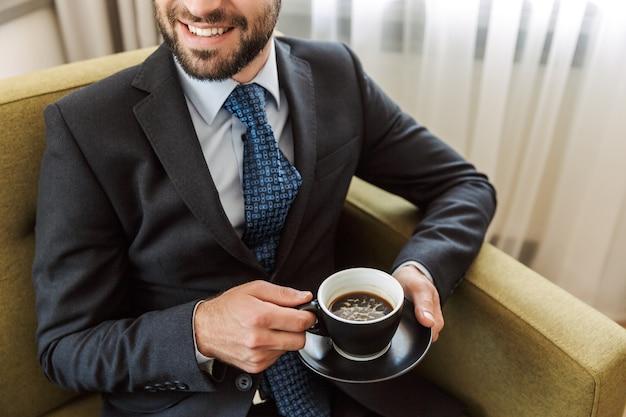 Atractivo joven empresario vistiendo traje sentado en una silla en la habitación del hotel, sosteniendo una taza de café
