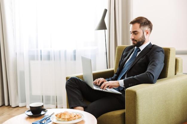 Atractivo joven empresario vistiendo traje sentado en una silla en la habitación del hotel, trabajando en la computadora portátil mientras desayuna
