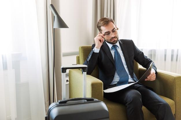 Atractivo joven empresario vistiendo traje sentado en una silla en la habitación del hotel, trabajando con documentos