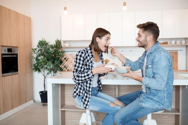 Atractivo joven feliz y mujer en la cocina, desayunando, pareja juntos en la mañana, sonriendo