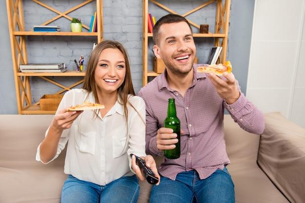 Atractivo joven feliz y una mujer viendo la televisión con cerveza y pizza