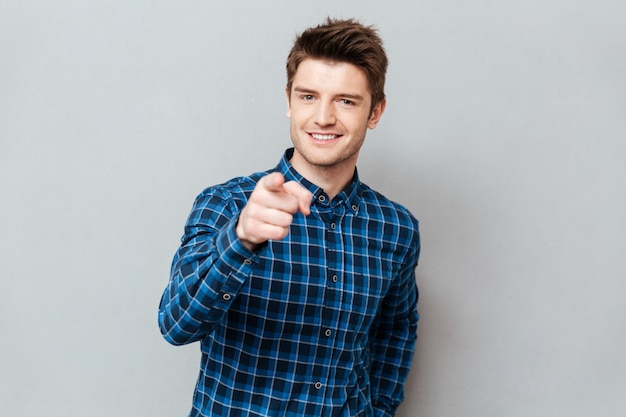 Atractivo joven feliz de pie sobre la pared gris y señalando