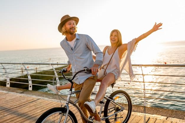 Atractivo joven hombre y mujer viajando en bicicleta, pareja romántica en vacaciones de verano junto al mar al atardecer, traje de estilo boho hipster, amigos divirtiéndose juntos