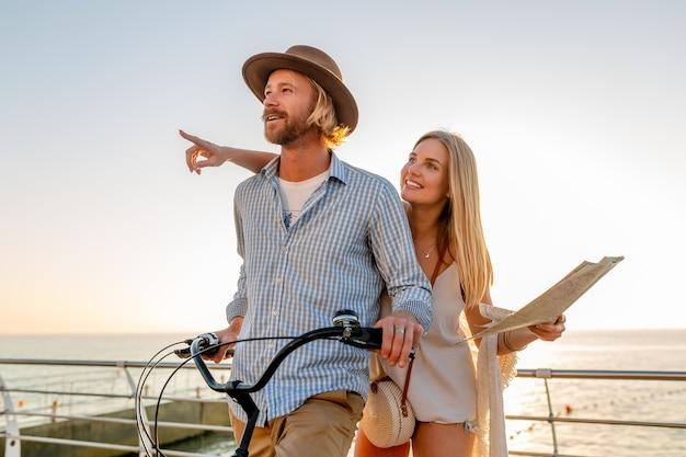 Atractivo joven hombre y mujer viajando en bicicleta, sosteniendo mapa, turismo, pareja romántica en vacaciones de verano junto al mar al atardecer, traje de estilo boho hipster, amigos divirtiéndose juntos