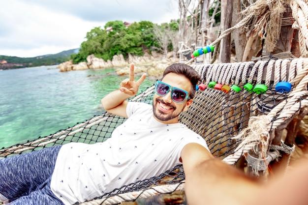 Atractivo joven latino guapo, hombre oscuro con barba en una hamaca de vacaciones hace selfie en el teléfono inteligente contra el mar disfrutando de la vida