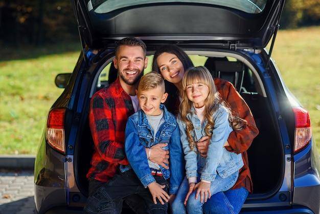 Atractivo joven madre y padre modernos y sus hijos adolescentes sonrientes que se sientan juntos en la cajuela del automóvil negro y mirando a la cámara