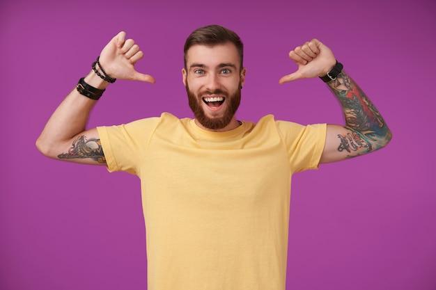 Atractivo joven morena barbudo con tatuajes levantando las manos y mostrándose a sí mismo con los pulgares, sonriendo ampliamente con confianza en sí mismo, de pie en púrpura en ropa casual