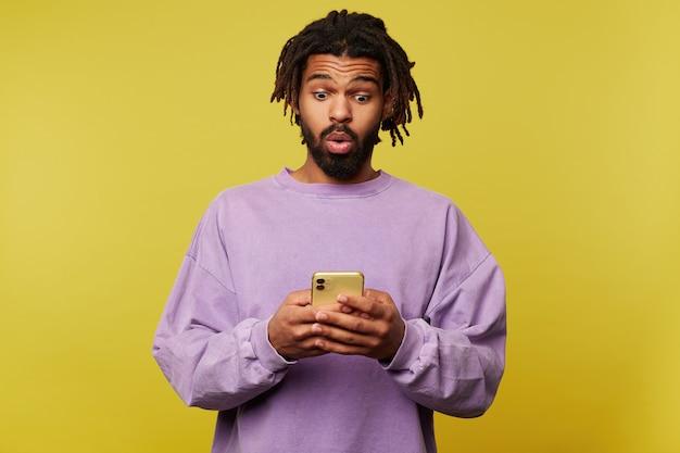 Atractivo joven de ojos abiertos morena de piel oscura levantando las cejas con sorpresa mientras lee noticias inesperadas en su teléfono inteligente, aislado sobre fondo amarillo