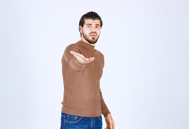 Atractivo joven de pie y dando su mano para apretón de manos