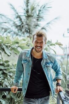 Atractivo joven posando en un lugar tropical, sobre un fondo de palmeras y vegetación
