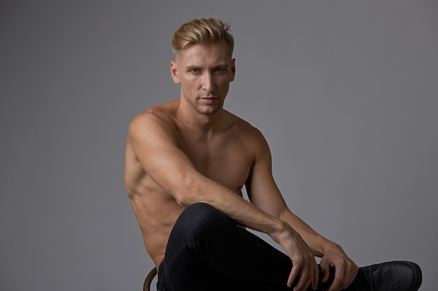 Atractivo joven posando con el torso desnudo sentado en una silla