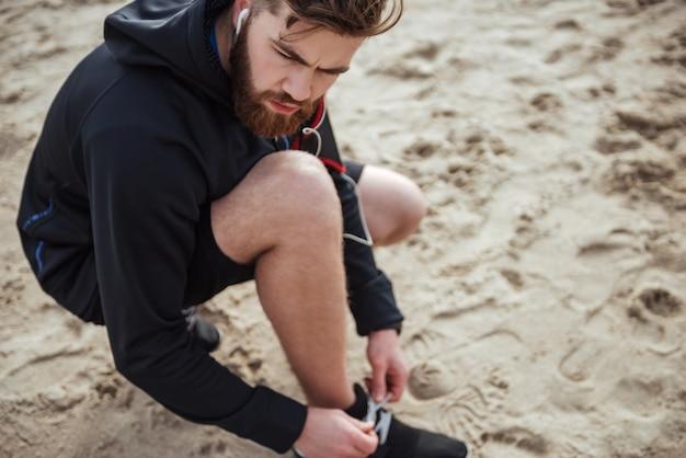 Atractivo joven preparándose para trotar en la playa desde arriba retrato