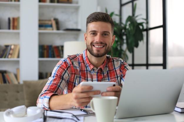 Atractivo joven sentado en el escritorio en la oficina en casa y usando el teléfono móvil para comprobar las redes sociales.