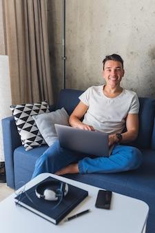Atractivo joven sentado en el sofá en casa trabajando en la computadora portátil en línea