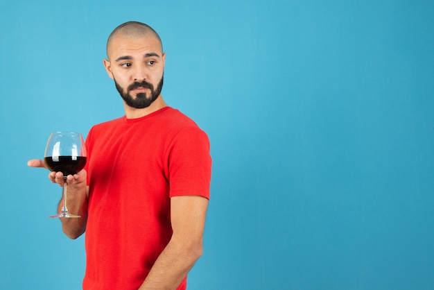 Atractivo joven sosteniendo una copa de vino tinto contra la pared azul.