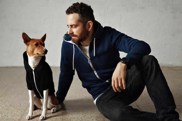 Un atractivo joven y su perro bassenji con sudaderas con capucha a juego se sientan en el suelo junto a la pared blanca