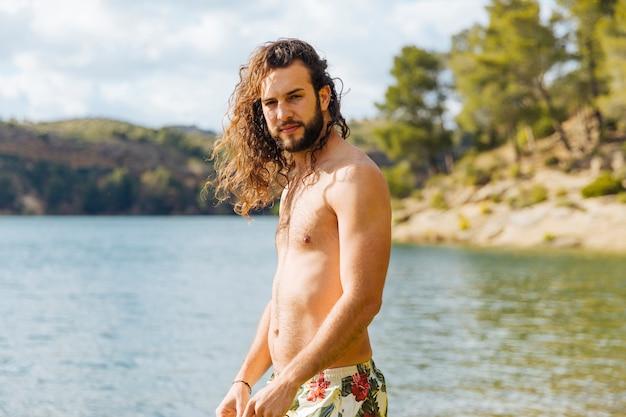 Atractivo macho joven descansando en el lago