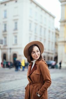 Atractivo en moderno abrigo marrón posando en la calle en el centro de la ciudad.