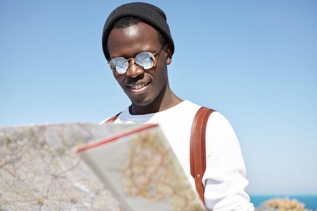 Atractivo y moderno joven turista negro en tonos redondos y sombreros mirando el mapa de papel en sus manos con interés, leyendo información sobre la ciudad donde está pasando las vacaciones de verano en