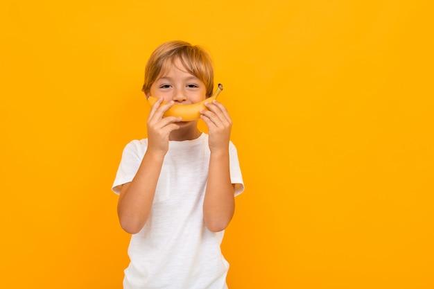Atractivo muchacho europeo en una camiseta blanca con una banana en sus manos sobre una pared naranja
