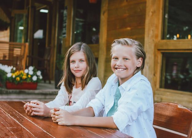 Atractivo muchacho rubio preadolescente con ojos azules en camisa blanca con hermana sentada en la mesa