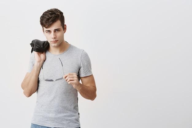 Atractivo, musculoso, confiado hombre posando en interiores. chico guapo con estilo con corte de pelo moderno con chaqueta de cuero negro sobre su hombro, con gafas de sol en la mano.