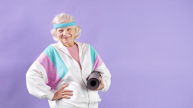Atractivo pensionista plantea sosteniendo una estera de yoga.