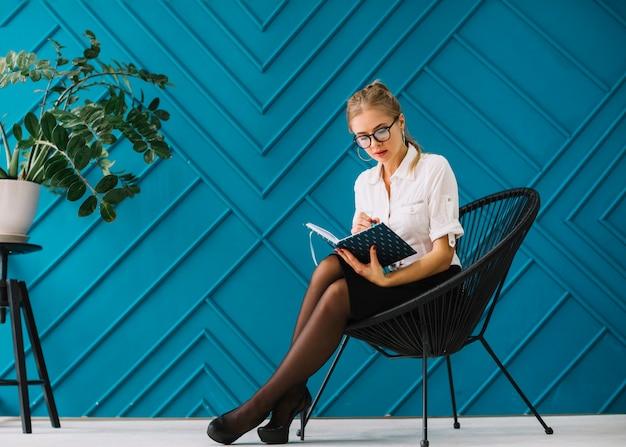 Un atractivo psicólogo sentado en la silla tomando notas en la oficina.