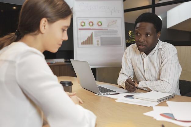Atractivo reclutador masculino de piel oscura entrevistando nerviosa joven mujer caucásica