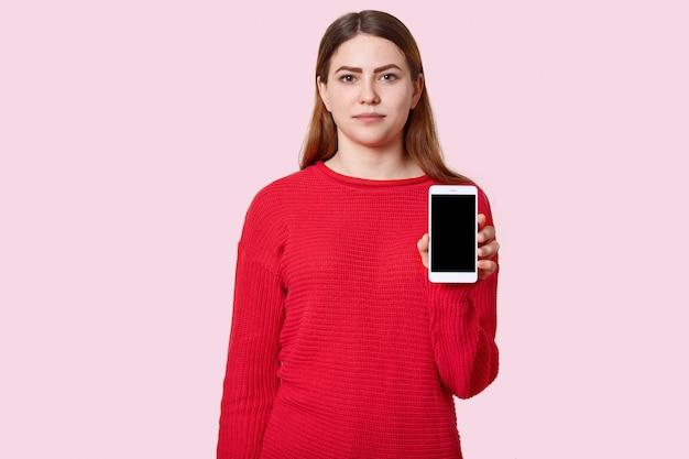 Atractivo serio joven europeo adolescente con el pelo largo, vestido con un jersey rojo suelto, tiene teléfono celular moderno con negro vacío