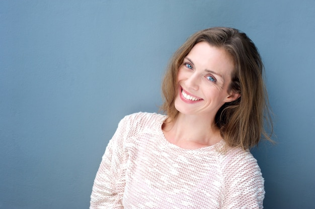 Atractivo sonriente mediados de mujer adulta sobre fondo azul
