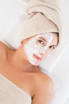 Atractivo tener crema blanca en su cara en el centro de spa