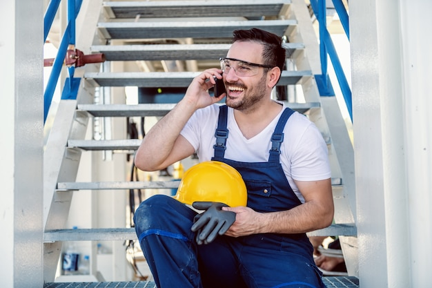 Atractivo trabajador caucásico sonriente en monos sentado en las escaleras y hablando por el teléfono inteligente. refinería exterior.