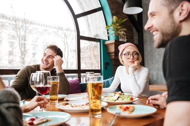 Atractivos amigos felices sentados en la cafetería