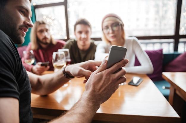 Atractivos amigos sentados en la cafetería y mirando el teléfono.