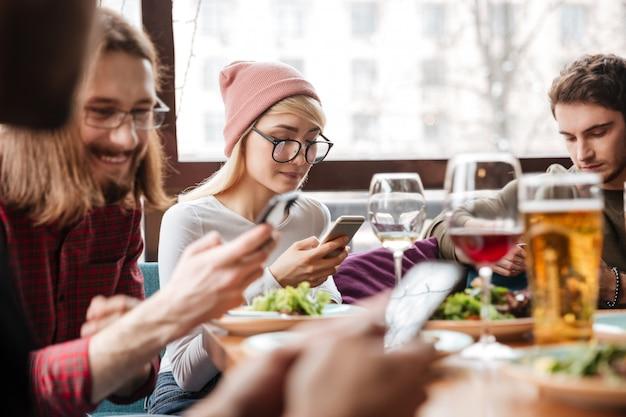 Atractivos amigos sentados en la cafetería y utilizando teléfonos móviles.