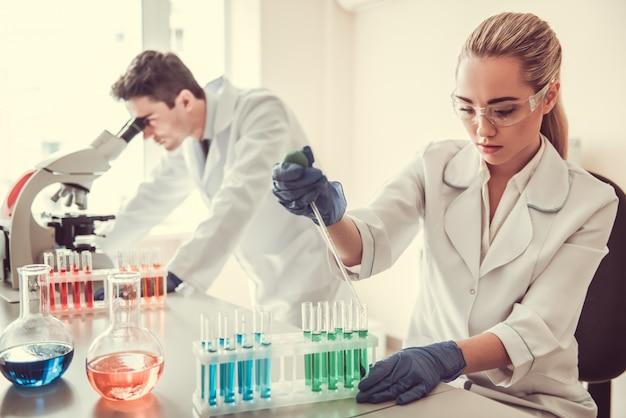 Atractivos médicos trabajan con tubos de ensayo.