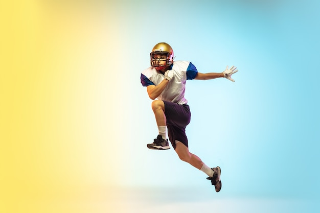 Atrapando. jugador de fútbol americano aislado en gradiente en luz de neón.