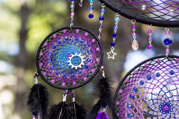 Atrapasueños hechos a mano con hilos de plumas y cuentas colgando de la cuerda.
