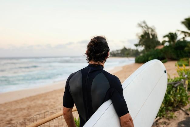 Desde atrás, hombre surfista tiro al aire libre