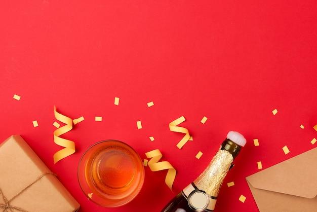 Atributos de fiesta vuelan desde una botella de vino champán sobre fondo rojo.