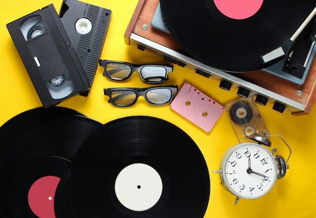 Atributos planos de estilo retro, medios de los 80. reproductor de vinilo, cintas de video, cintas de audio, discos, gafas 3d, reloj despertador vintage, libros antiguos sobre fondo amarillo. vista superior