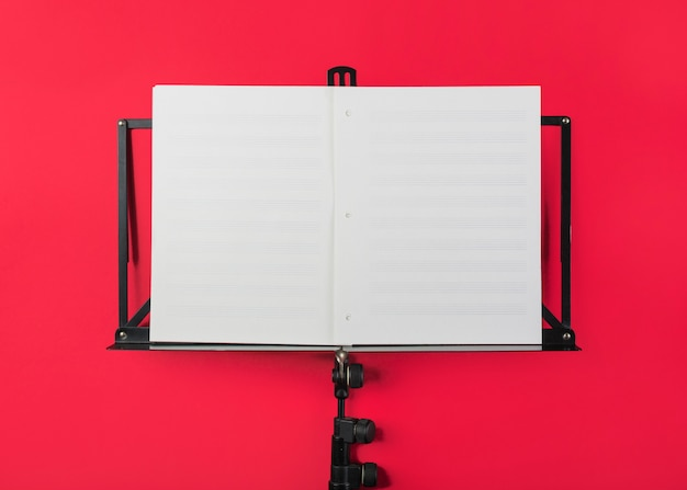 Atril musical con página musical blanca en blanco sobre fondo rojo