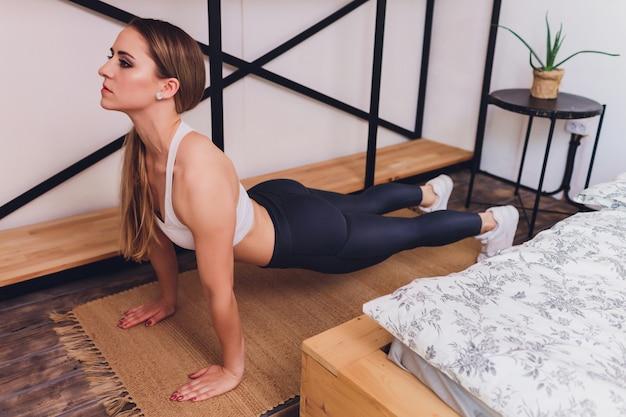 Attrctive fitness mujer haciendo ejercicios de estiramiento en casa, como parte de un estilo de vida saludable sin ir al gimnasio.